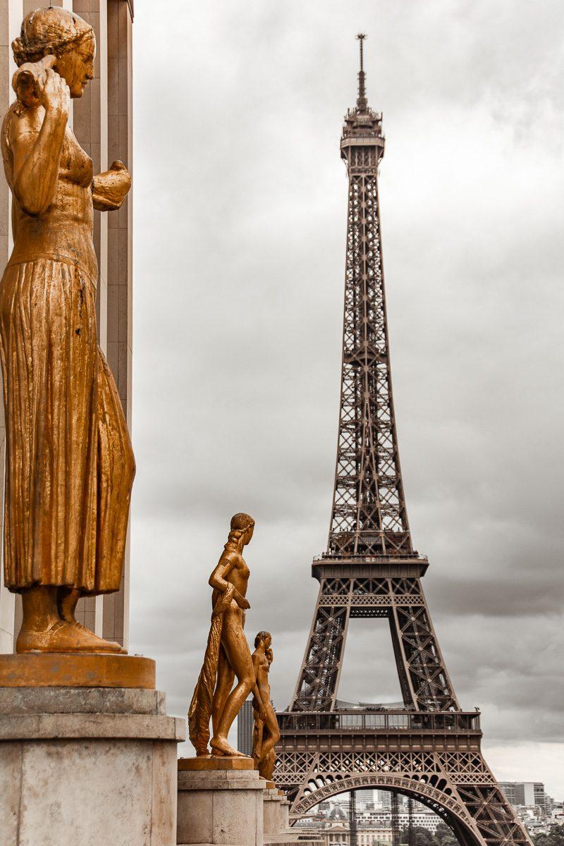 Eiffelturm mit goldenen Statuen im Vordergrund – Wandbild Eiffelturm