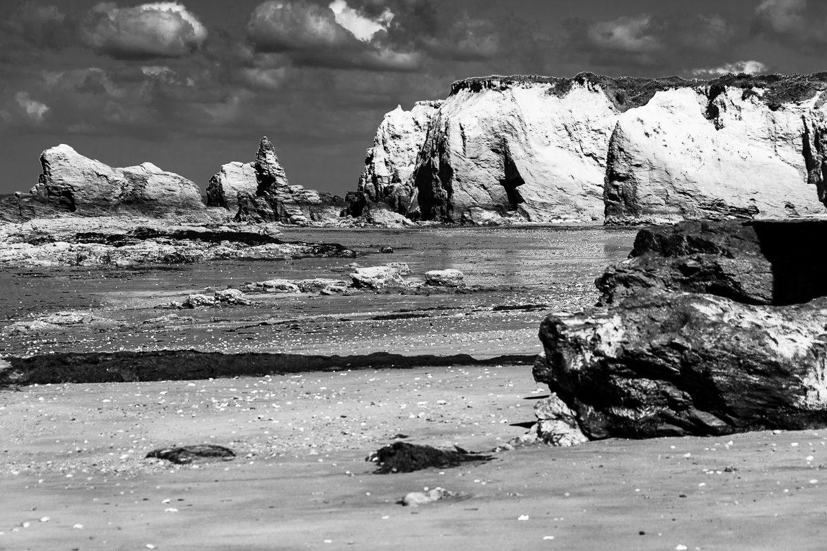 Schroffe Felsen an der wilden Küste der Bretagne, Schwarzweißfotografie im Querformat.