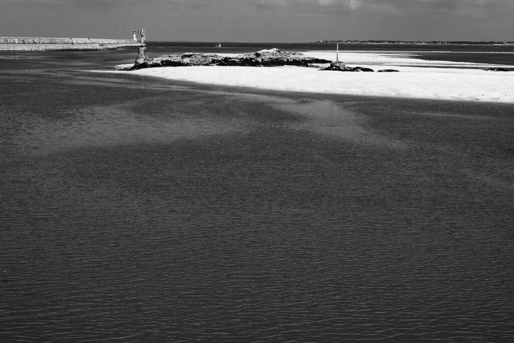 Hafeneinfahrt mit Sandbänken und Leuchtturm – Bretagne