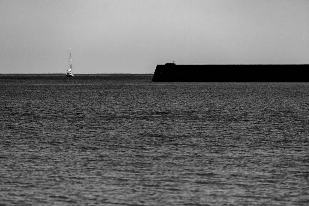Segelboot an Kaimauer beim Auslaufen – Wandbild mit Segelboot