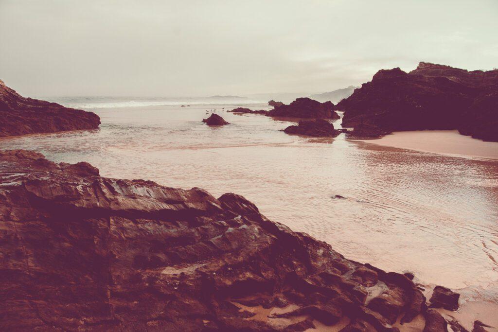Wilde Atlantikküste - Felsen mit Sandstrand und Meeresbrandung - Sines Portugal Wandbild